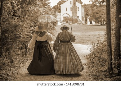 Two women wearing antebellum dresses walk with parasols on the grounds of a 19th Century historic site.