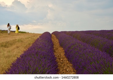 Two women wearing long dresses of yellow and white walk along a dirt path beside rows of blooming, vibrant, purple lavanders extending towards the horizon under a cloudy Provençal sky.