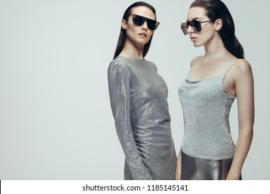 Two women wearing silver trendy outfit with sunglasses standing on grey background. Female model in futuristic look in studio.