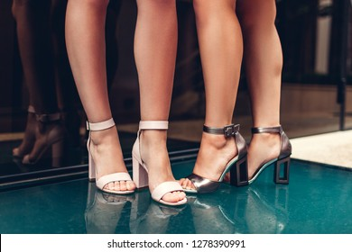 Two women wearing stylish shoes outdoors. Summer street fashion concept. Leather footwear. Heels