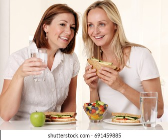 TWO WOMEN WEARING WHITE EATING LUNCH TOGETHER,SANDWICHES,GREEN APPLE AND GLASS OF WATER,WHITE INTERIOR