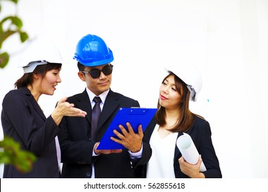Two Women wears white safety hard hat is dicussing  project with  the man in black suit who wears blue safety hard hat on white background.