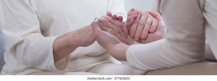 Two women in white clothes holding their hands, close up, panorama.