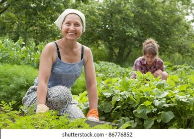 Two women working in her vegetable garden