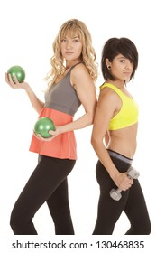 Two women working out one is lifting weighted balls the other weights.