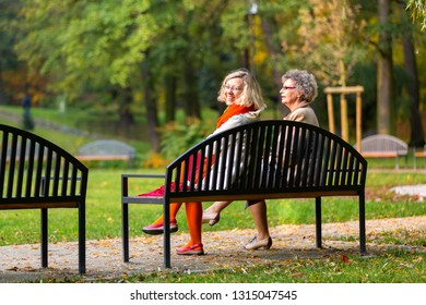 two women, younger and older, in the park sitting on a bench