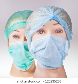 two women's dummy doctor heads wearing textile surgical cap and medical protective mask