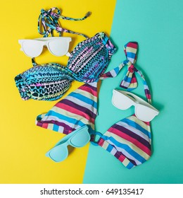 two women's swimwears and fashionable blue and white sunglasses for relaxing at the beach
