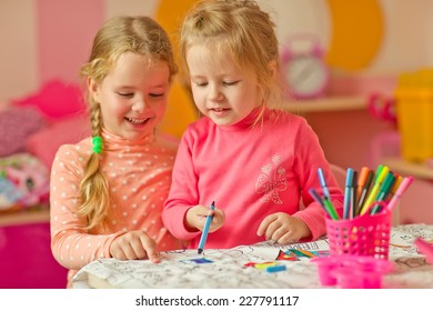 Two wonderful children draw with colored pencils