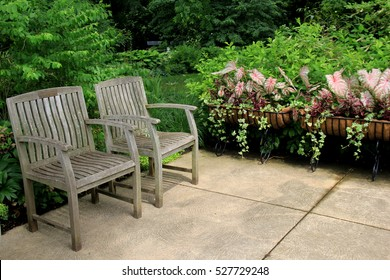 Two wood benches in courtyard of garden, where people can sit and unwind for a time, from their otherwise busy lives.