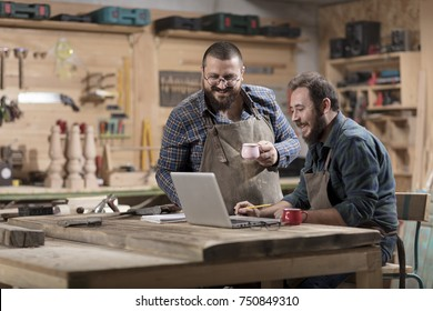 Two wood designer working with laptop in workshop.
