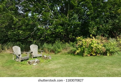 Two wooden adirondack chairs next to a fire pit with lush trees and plants in the background.
