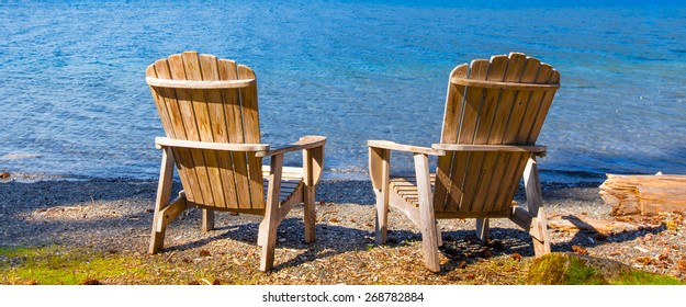Two wooden adirondack chairs on the shore of a lake facing the water. Viewed from the back.