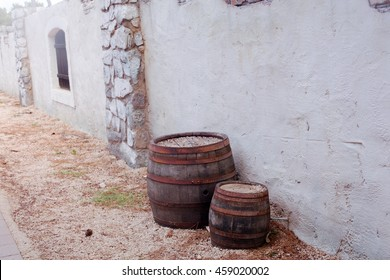 two wooden antique barrels standing near a stone wall in the bushes