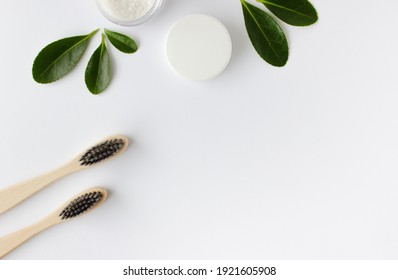 two wooden bamboo eco friendly toothbrushes, dentifrice and green leaves on white background.