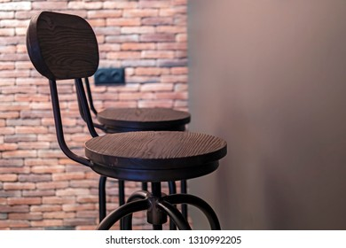 Two wooden bar stools, brick wall background