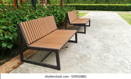 Two wooden benches on cement floor at park