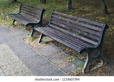 Two wooden benches at the pavement a park