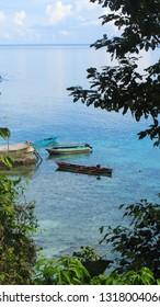 Two wooden boats on clear beach near the dock, taken in Saleman Village, Seram island, Indonesia