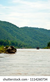 Two wooden boats are on the Mekong in Laos. The water is muddy. On either side are hills covered with forest. Some rocks are in the foreground.