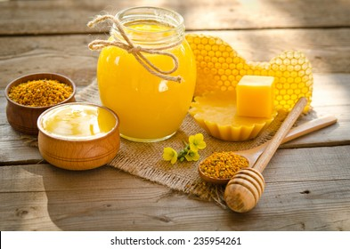 two wooden bowls one with honey another with pollen.The bank of honey stay near honeycombs,wax,wooden spoon with honey and dipper
