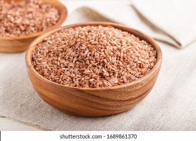 Two wooden bowls with unpolished brown rice on a white wooden background and linen textile. Side view, close up, selective focus.