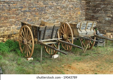 two wooden carts against a stone wall