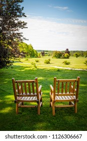 Two wooden chairs on lush green lawn with view of countryside in summer