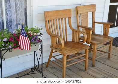 Two wooden chairs on old front porch with flowers and american flag