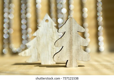 Two wooden Christmas trees on wooden table, reflections on background, Christmas chains