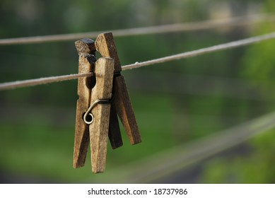 Two wooden clothes pins on cord outdoors