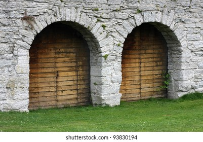 Two wooden doorways in solid stone wall.