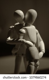 Two wooden dummies hugging each other. Close up. Black and white photo.
