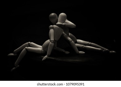 Two wooden dummies lying on the ground kissing. Horizontal. Black background
