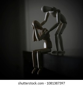 two wooden dummies, the one sitting desperately with his hands to his face is comforted by the other standing behind him