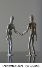 Two wooden dummies shaking hands