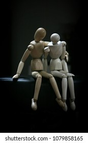 Two wooden dummies sitting close together.  One embraces the other who has a shy posture. Black background. Vertical photo,
