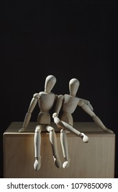 two wooden dummies sitting on a wooden box, one hugs the other who has his legs crossed. Black background. Vertical. Room for text.