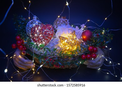 Two wooden hands hold a basket full of Christmas ornaments and decorations against a dark background with Christmas lights, mistletoe and many colors.