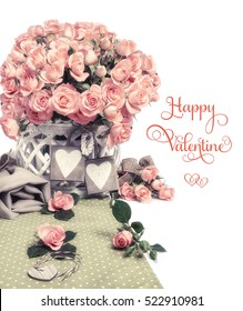 """Two wooden heart tags among beautiful pink roses, isolated on white. Tect """"Happy Valentine"""" on white background. You can replace it with your own greeting.This image is toned."""