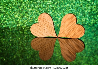 Two wooden hearts in front of a green background form a shamrock on a reflecting surface