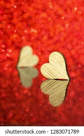 Two wooden hearts in front of a red background and on a reflecting background