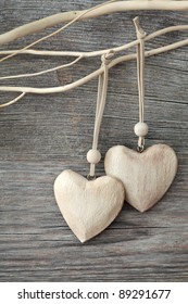 Two wooden hearts on grey background