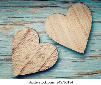 Two wooden hearts placed nicely on a turquoise vintage wood background