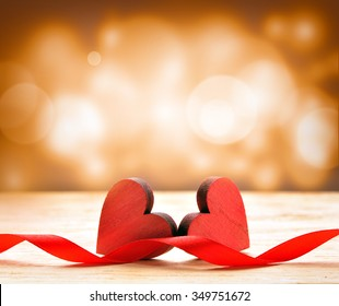 Two wooden hearts and red ribbon. Background for Valentines Day.