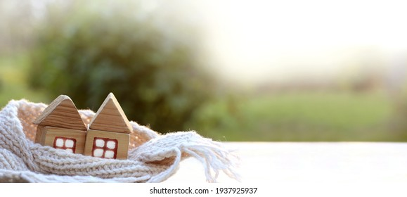 two wooden house in scarf on the background of a blurred landscape. cozy heating plan two in one