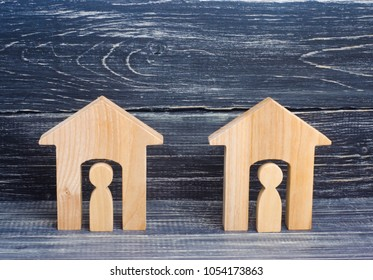 Two wooden houses with people on a black background. The concept of the district, its neighbors. Good-neighborly relations. Affordable housing for young families, construction and sale of real estate