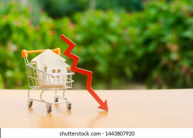 Two wooden houses in a trading cart and red arrow down. falling real estate market. Reduced interest in the mortgage. A decline in property prices and apartments. Low interest rates on mortgage loans.