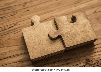 two wooden jigsaw puzzle couple of pieces texture pattern on wood texture background of trunk. empty copy space for inscription or objects. business, education  concept