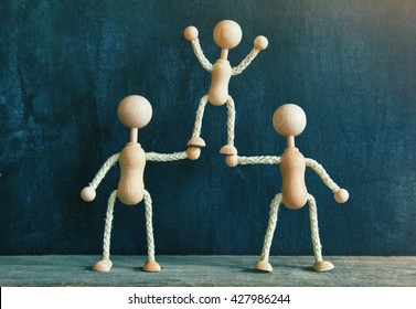 Two wooden little men supporting the third. Concept of teamwork, friendship, support or family